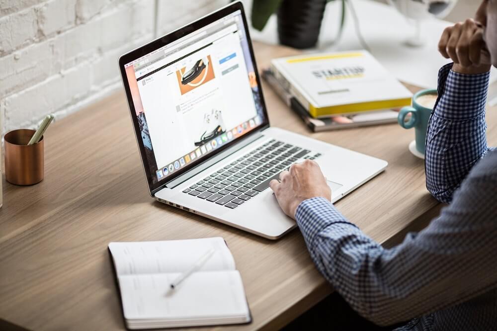 Мужчина за ноутбуком смотрит на сайт