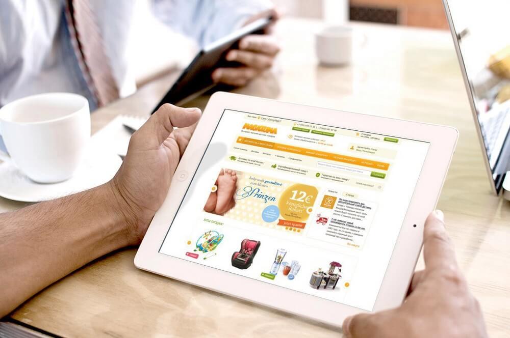 Открытая страница доходного сайта на планшете в мужских руках