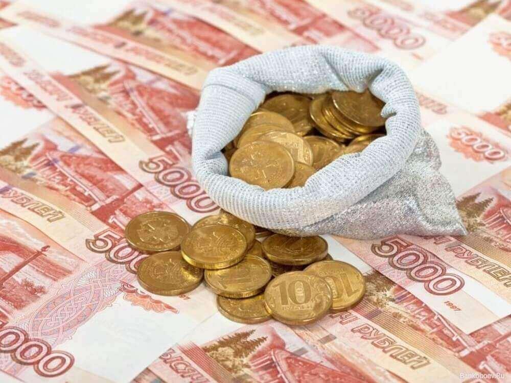Монеты на фоне пятитысячных купюр